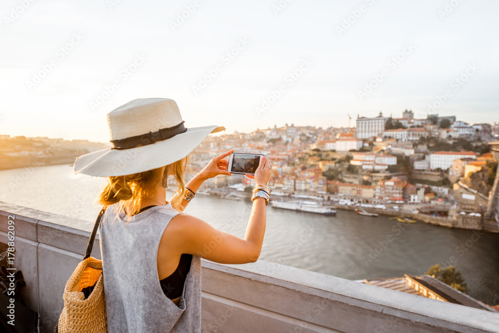 Fototapety, obrazy: Young woman tourist photographing with phone beautiful landscape view on the old town with river and famous iron bridge in Porto city, Portugal