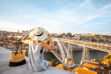 Young Woman Tourist Enjoying Beautiful Landscape View On The Old Town With River And Famous Iron Bridge During The Sunset In Porto City, Portugal