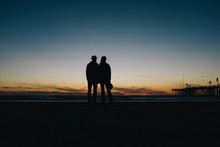 Silhouette Couple Standing On Beach During Sunset
