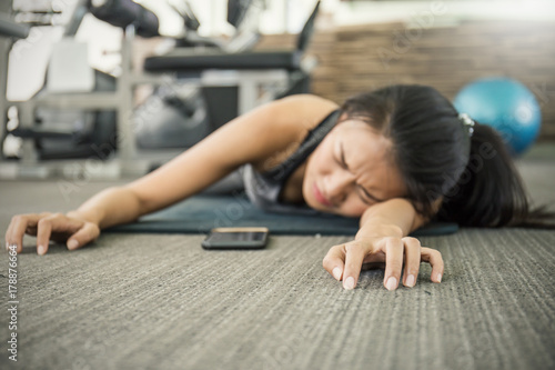 Asian tan woman fainting to the floor during her exercise at the sport club gym Wallpaper Mural