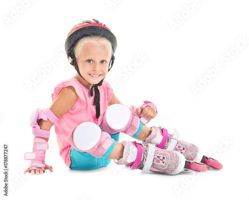 Girl on roller skates sitting against white background