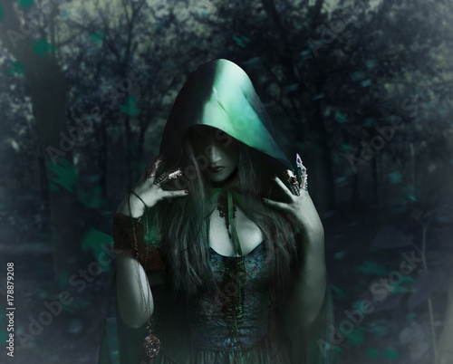 Stampa su Tela Beautiful sorceress in green cloak holding antique watch standing in the night forest photo