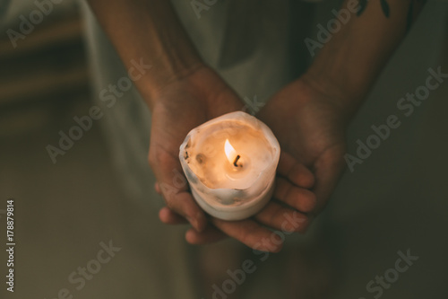 Tender and sensual woman hands hold small white wax candle slowly burning with t Wallpaper Mural