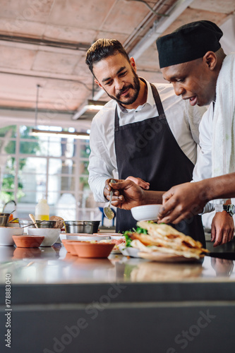 Poster Cuisine Chefs cooking new food dish in kitchen