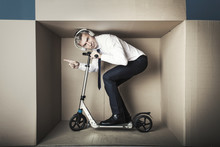 Middle-aged Businessman In Small Office Box Tries To Ride A Scooter