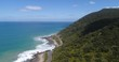 Scenic coastal drive on Great Ocean road along foresty hillsides and Souther ocean waters on a sunny day.