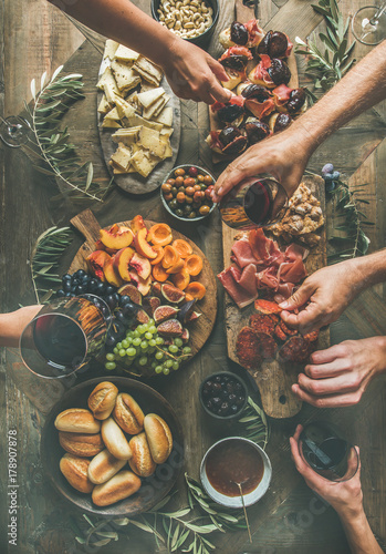 Overhead view of friends hands eating and drinking together