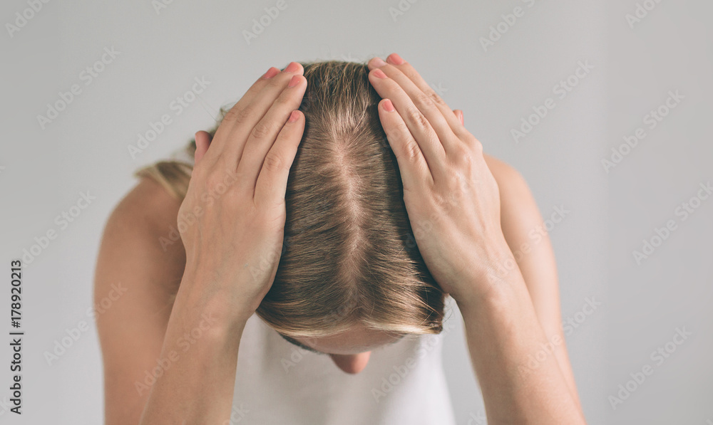 Fototapeta Women's hair is a top view close-up. Blonde woman is wearing shirt isolated on white.