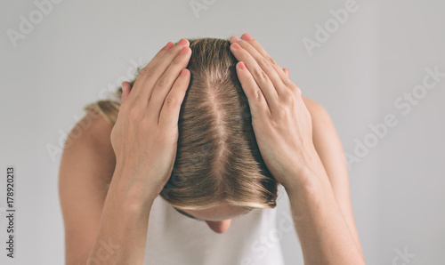 Women's hair is a top view close-up. Blonde woman is wearing shirt isolated on white.