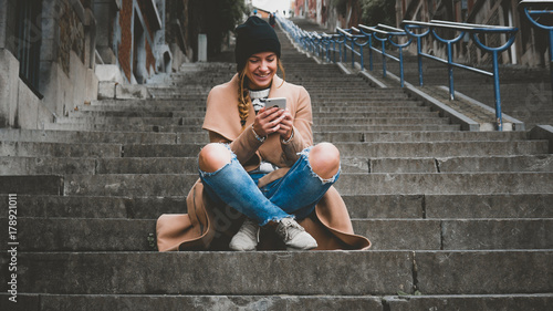 Lifestyle portrait of a beautiful Caucasian female sitting on a stairway and texting on her phone. Horizontal orientation