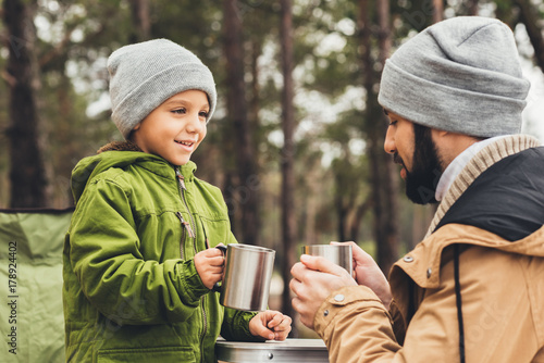 Obraz father and son with cups of tea outdoors - fototapety do salonu