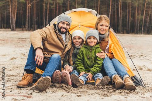 Obraz na dibondzie (fotoboard) rodzina siedzi obok namiotu kempingowego