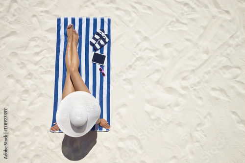 Obraz Summer holiday fashion concept - tanning woman wearing sun hat at the beach on a white sand shot from above - fototapety do salonu