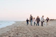 Family Walking With Dog At Sea...