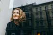 canvas print picture - Junge blonde Frau schaut lächelnd aus dem Fenster