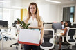 Fired female employee holding box of belongings in an office