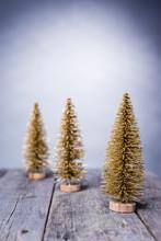 Tre Gyllene Julgranar På Rustikt Trä Bord Med Går Bakgrund