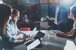 Business people brainstorming concept.Coworkers working at night office.Horizontal, flares effect.Blurred background.