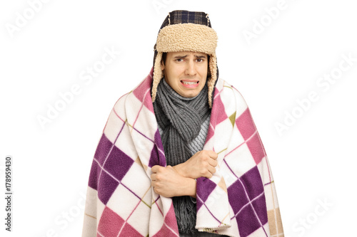 Foto  Young man covered with a blanket feeling cold
