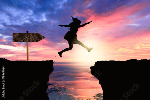 Fotografie, Obraz  courageous and motivated woman jumps the crevasse