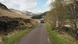 Aerial tracking shot of a car driving through the Scottish Highlands near Glenfinnan