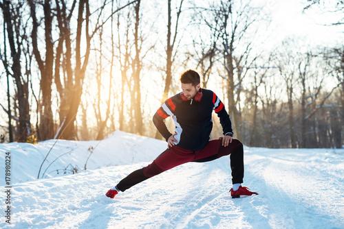 Zdjęcie XXL Młoda sportive mężczyzna rozciągania noga i rozgrzewkowy z hełmofonami na śniegu zakrywaliśmy zimy drogę.