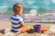 Little boy sitting on the beach with his toys and looks into the distance