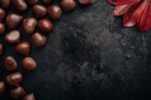 Tasty Chestnuts On Dark Black Rustic Background. Pile Of Fresh Chestnuts Ready To Roast Shot Over Black Antique Background. Top View, Copy Space.