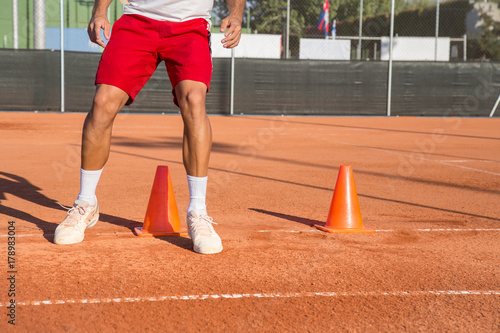 Professional tennis player warming up by dodging cones in zigzag manner.
