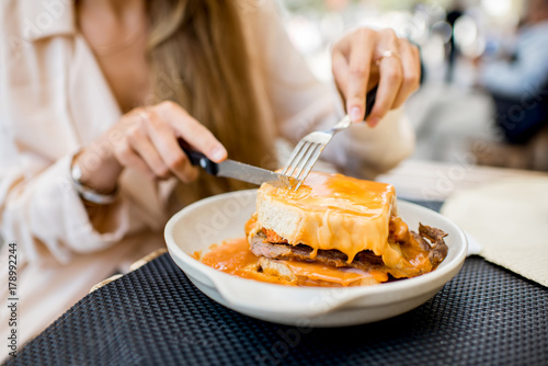 Foto  Eating traditional portuguese meat sandwich with tomato sauce called francesinha
