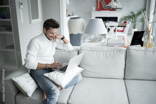 Plakat Przystojny mężczyzna ono uśmiecha się jego laptopu obsiadanie na leżance w domu