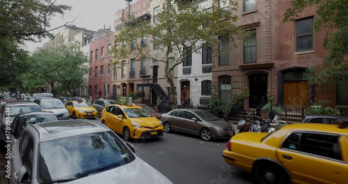 Foto op Aluminium New York Wide view exterior shot of a typical generic New York City block with apartment buildings yellow taxi cab traffic and parked cars lining side of street.