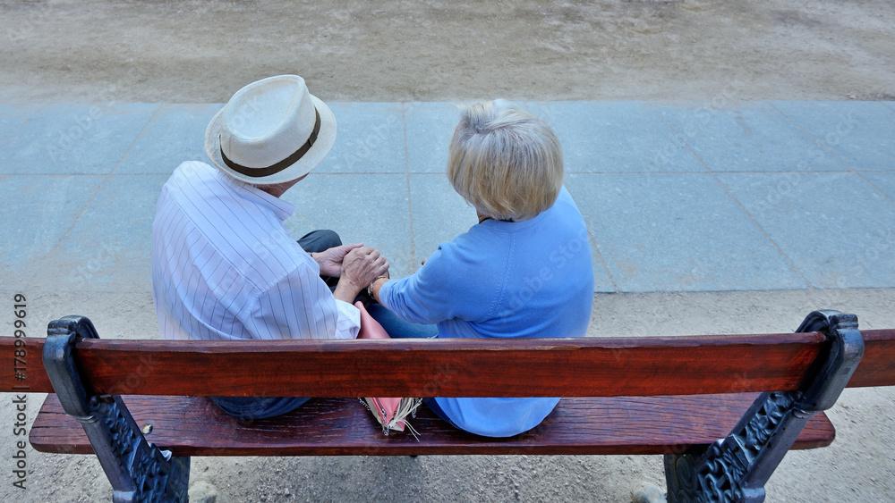 Fototapeta Pair of older people sitting on bench.