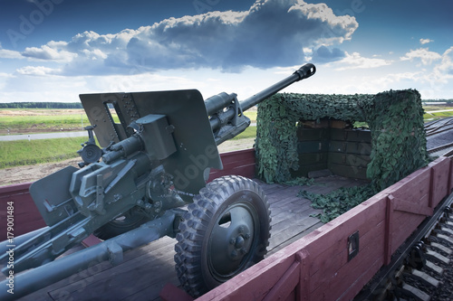 Old green russian artillery field cannon gun on the train car under the blue sky Canvas Print