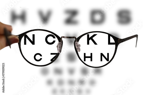 Fotomural myopia correction glasses on the eye chart letters background