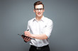 Handsome young businessman in costly watch, black glasses and white shirt hold tablet and pen