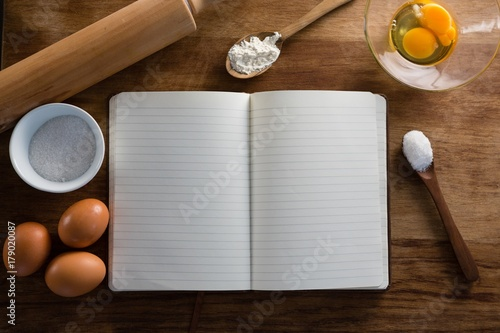 Book, eggs, flour, spoon and rolling pin kept on a table