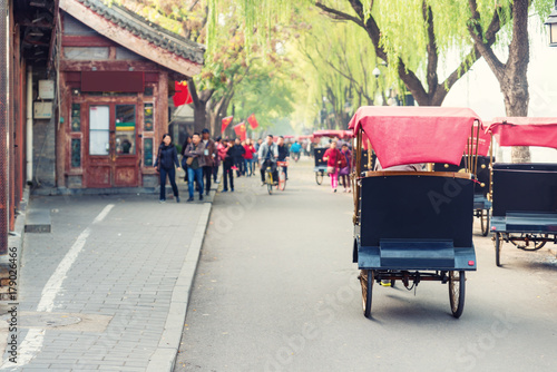 Stickers pour porte Pékin Tourists riding Beijing traditional rickshaw in old China Hutongs in Beijing, China.