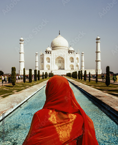 Fényképezés  Woman in red scarf looking at Taj Mahal in Agra, Uttar Pradesh, India