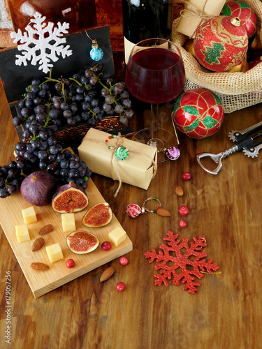 Foto op Plexiglas Milkshake Cheese and figs on a wooden board, red wine in a glass, grape and Christmas attributes around. Christmas table laying