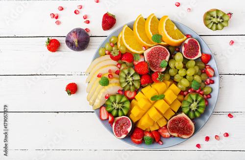 Foto op Aluminium Vruchten Platter fruits and berries. Mango, kiwi, fig, strawberry, grapes, pear and orange. Vegan cuisine. Dietary menu. Flat lay. Top view