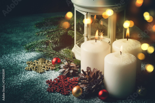 Foto op Canvas Kerstmis Three Christmas burning candles and lantern on dark turquoise background