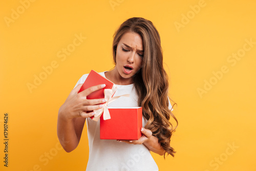 Portrait of an upset disappointed girl opening gift box Fototapet
