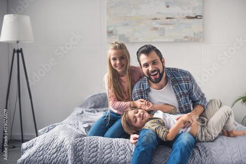 Fototapeta father and kids resting on bed obraz na płótnie