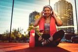 Fototapeta Londyn - Young Woman Listening Music After Training on Urban Sport Court