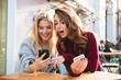 canvas print picture - Two excited young girls using mobile phones
