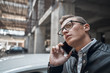 Close-up. A young handsome man talking on the phone. Standing at the car parking