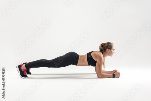 Fototapeta Balance and concentration. Strong blonde woman standing in plank obraz