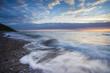 Ostsee im strahlenden Gegenlicht und bewegter See mit Steinen im Wasser und langer Belichtung im Sommer