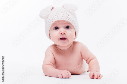 2b768e916c65 Cute baby girl lying naked on a white background wearing a hat in the form  of